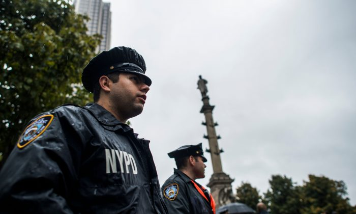 New York Police Department (NYPD) officers on the job. Two officers stand alert near the statue of Christopher Columbus at the Columbus Circle in New York on October 9, 2017, while a small group of people protest calling for the removal of the statue.  (JEWEL SAMAD/AFP/Getty Images)