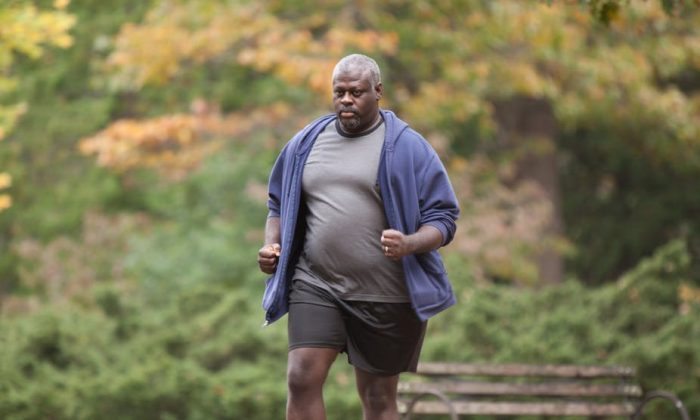A man who is overweight walking alone in a park. Walking with a doctor could be helpful for overweight patients. (Rudd Center for Food Policy and Obesity)