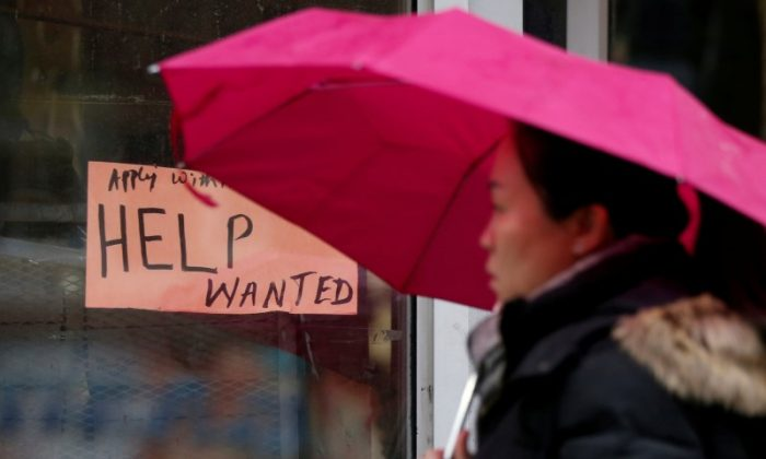 "A woman walks past a ""Help Wanted"" sign at a retail store in Ottawa on Nov. 2, 2017. (Reuters/Chris Wattie/File Photo)"