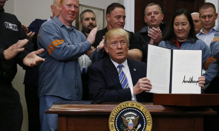 U.S. President DonaldTrumpholds up a proclamation during a White House ceremony to establish tariffs on imports ofsteel and aluminum at the White House in Washington on March 8, 2018. (Reuters/Leah Millis)