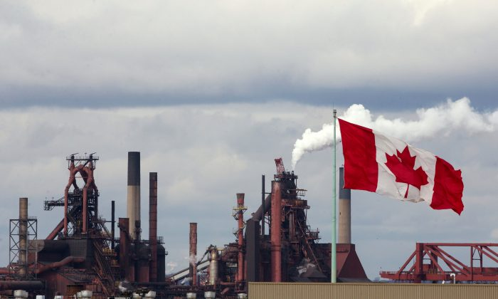 A Canadian flag flies above another industry site with ArcelorMittal Dofasco in the background in Hamilton, Ontario, Canada on March 9, 2018. (Reuters/Peter Power/File Photo)
