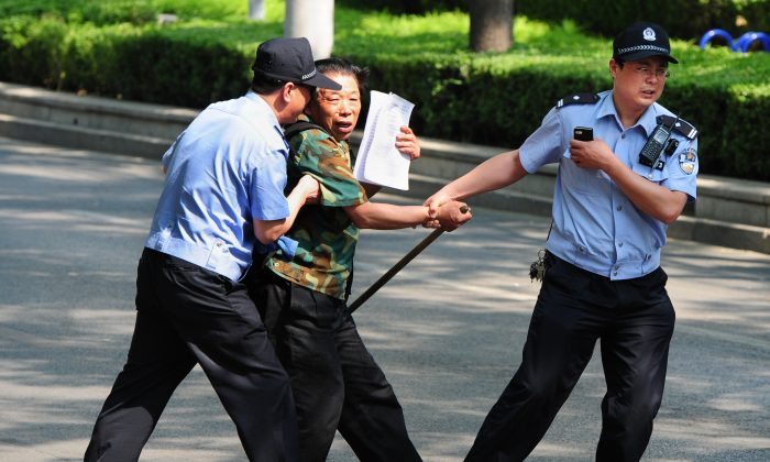 A petitioner is detained by police outside the Chaoyang Hospital where a group of people are protesting about medical and land grab issues in Beijing on May 8, 2012. (Mark Ralston/AFP/GettyImages)