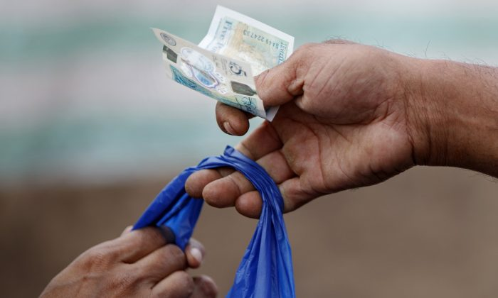 A customer uses a five-pound sterling note to pay a shopkeeper. Cash as a payment method isn't going away anytime soon in advanced economies, according to new research from the Bank of International Settlements. (Tolga Akmen/AFP/Getty Images)
