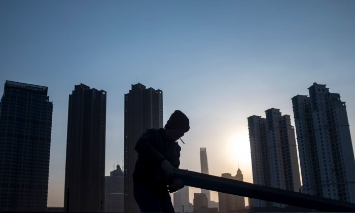 A man collects rubble on a construction site near the skyline of the Lujiazui Financial District in Shanghai, China on February 4, 2018. (Johannes Eisele/AFP/Getty Images)