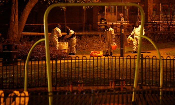 Members of the emergency services wearing protective clothing work next to a children's play area near the bench where former Russian intelligence officer Sergei Skripal and his daughter Yulia were found poisoned in Salisbury, Britain, March 13, 2018. (Reuters/Henry Nicholls)