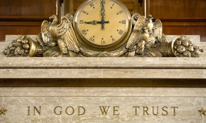 A clock and the motto 'In God We Trust' over the Speaker's rostrum in the U.S. House of Representatives chamber are seen in Washington, DC on Dec. 8, 2008. (Photo by Brendan Hoffman/Getty Images)