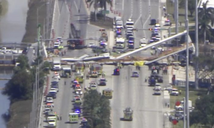 In this frame from video, emergency personnel work at the scene of a collapsed bridge in the Miami area, Thursday, Mar. 15, 2018. (WPLG-TV)