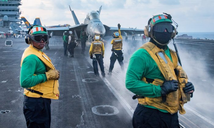 U.S. Sailors conduct flight operations on the aircraft carrier USS Carl Vinson (CVN 70) flight deck in South China Sea on April 8, 2017. (Mass Communication Specialist 3rd Class Matt Brown/U.S. Navy via Getty Images)