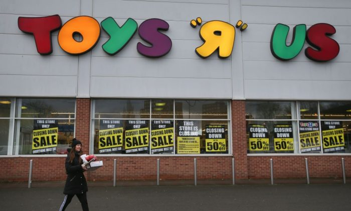 A customer walks out of a Toys r Us store with 'closing down sale' signs in the windows in south London on Feb. 9, 2018. (Daniel Leal-Olivas/AFP/Getty Images)