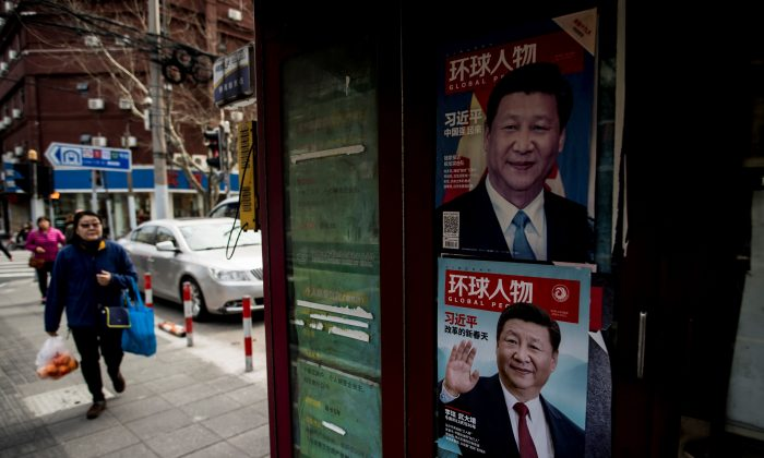 A woman passes a newspaper stand showing a magazine with a picture of Chinese leader Xi Jinping on its cover, in downtown Shanghai, China, on March 12, 2018. (Johannes Eisele/AFP/Getty Images)