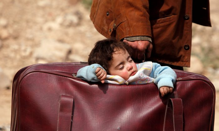 A child sleeps in a bag in the village of Beit Sawa, eastern Ghouta, Syria March 15, 2018. (Reuters/Omar Sanadiki)