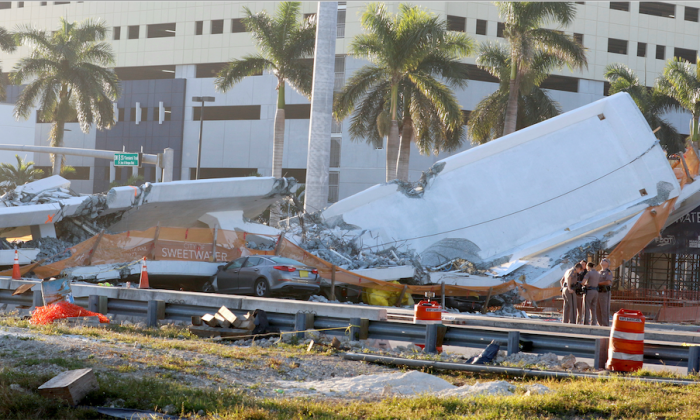 Police officers are seen next to a collapsed pedestrian bridge at Florida International University in Miami, Florida on March 16, 2018. (Reuters/Joe Skipper)