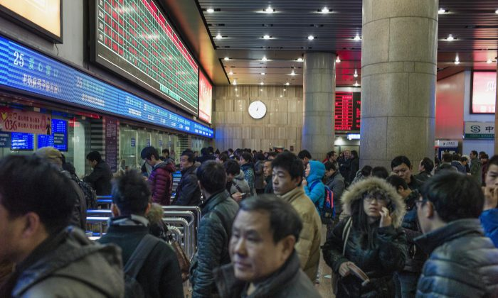 Chinese travelers queue to buy train tickets to head home for the Lunar New Year at the Beijing Train Station on Feb. 4, 2015. (Fred Dufour/AFP/Getty Images)