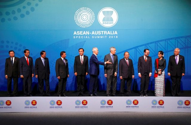 Australia's Prime Minister Malcolm Turnbull gestures to ASEAN leaders Laos' Prime Minister Thongloun Sisoulith, Indonesia's President Joko Widodo, Cambodia's Prime Minister Hun Sen, Brunei's Sultan and Prime Minister Sultan Bokliah, Thailand's Prime Minister Prayut Chan-O-Cha, Singapore's Prime Minister Lee Hsien Loong, Vietnam's Prime Minister Nguyen Xuan Phuc, Philippines' Secretary of Foreign Affairs Alan Peter Cayetano, Burma's State Counsellor Aung San Suu Kyi and Malaysia's Prime Minister Najib Razak to leave the stage after posing for the Leaders Welcome and Family Photo at the one-off summit of 10-member Association of Southeast Asian Nations (ASEAN) in Sydney, Australia, March 17, 2018.     (Reuters/David Gray)
