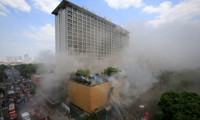 Firefighters douse water after a fire engulfed the Manila Pavilon hotel in Metro Manila, Philippines March 18, 2018. (Reuters/Romeo Ranoco)