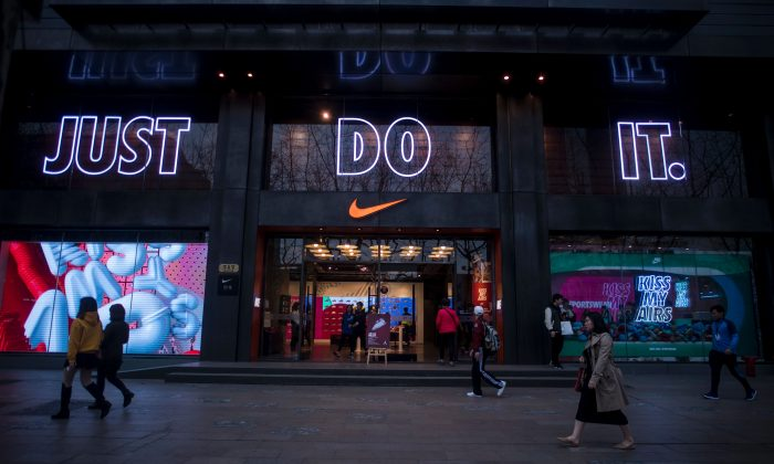 People pass by the flagship store of sporting-goods giant Nike in Shanghai, China, on March 16, 2017. (Johannes Eisele/AFP/Getty Images)