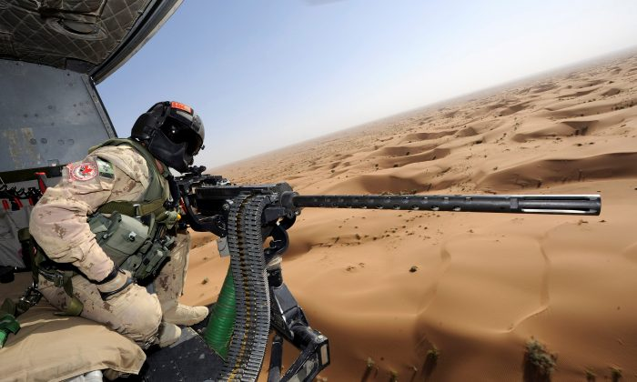 Canadian Forces door gunner Sergeant Chad Zopf leans out of a CH-146 Griffon helicopter during a training exercise in Kandahar district, Afghanistan June 18, 2011. (Sgt Matthew McGregor/Canada Department of National Defence/Handout via Reuters)