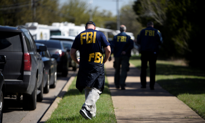 FBI agents walk towards a crime scene on Mission Oaks Boulevard following an explosion in Austin, Texas, U.S., March 19, 2018. (Reuters/Sergio Flores)