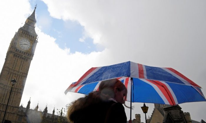 FILE PHOTO: A woman carries a British union flag design umbrella as she walks past the Houses of Parliament in London, on Apr. 26, 2017. (REUTERS)Toby Melville