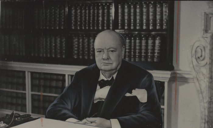 Sir Winston Churchill at his desk in the cabinet room of No. 10 Downing St. at age 79. Churchill's painting of Emerald Lake in the Rocky Mountains sold for $87,000 despite being damaged. (The Canadian Press)