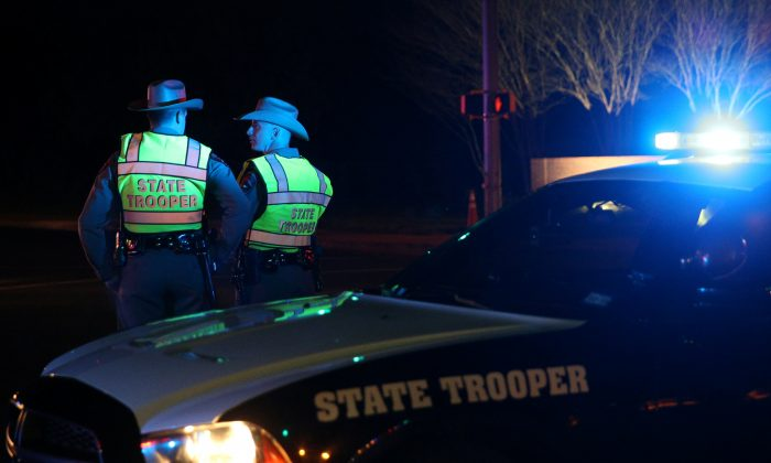 Texas state troopers keep watch at a checkpoint as nearby law enforcement personnel investigate an incident that they said involved an incendiary device in the 9800 block of Brodie Lane in Austin, Texas, U.S., March 20, 2018. (Reuters/Loren Elliott)