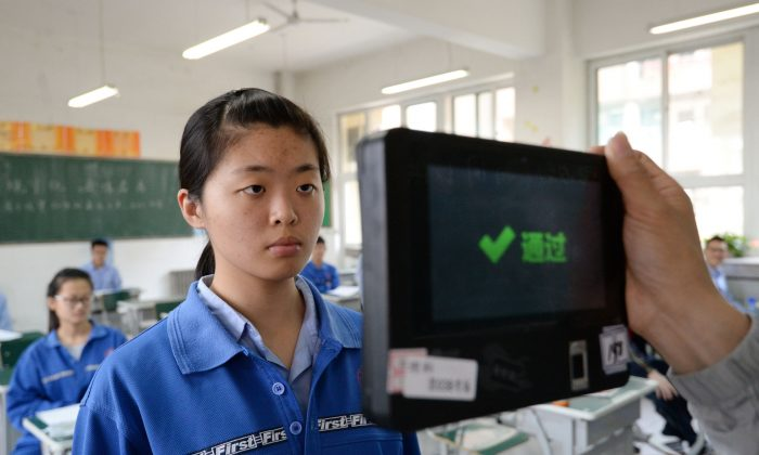 A teacher uses a fingerprint and facial recognition machine to check a student before a simulated college entrance exam in China's northern Hebei Province on June 6, 2017.
