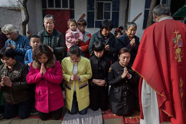 """Chinese Catholic worshippers wait to take communion at the Palm Sunday Mass during the Easter Holy Week at an """"underground"""" or """"unofficial"""" church near Shijiazhuang, Hebei Province, China, on April 9, 2017. (Kevin Frayer/Getty Images)"""