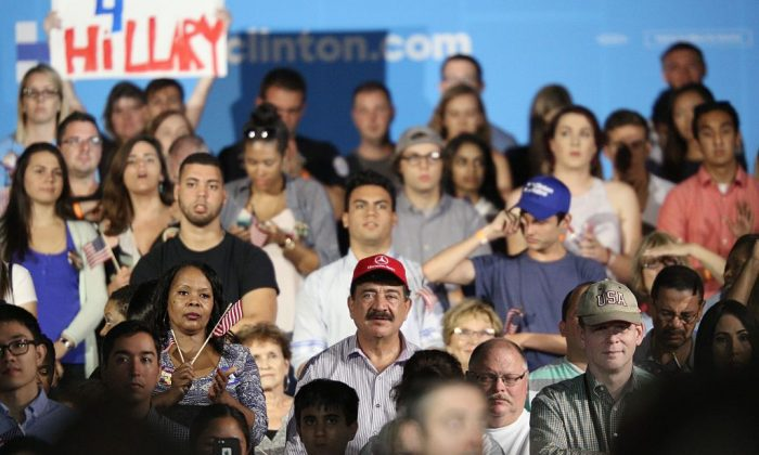 Seddique Mateen (C-red ball cap), whose son shot and killed 49 people and injured 53 others inside the Pulse nightclub in June, sits with supporters at a rally for Democratic Presidential nominee Hillary Clinton at the Osceola Heritage Park in Kissimmee, Florida on August 8, 2016. (GREGG NEWTON/AFP/Getty Images)