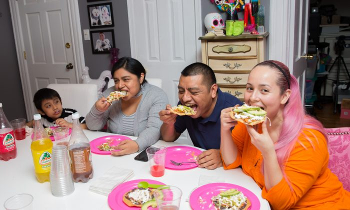 Angie Vargas (R) and her family take a big bite out of the Tostadas de Tinga (shredded spicy chicken tostadas). (Benjamin Chasteen/The Epoch Times)
