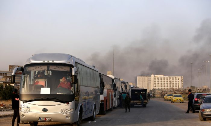 A convoy of buses that carry rebels and their families waits at Harasta highway outside Jobar, in Damascus, Syria March 26, 2018. (Reuters/Omar Sanadiki)