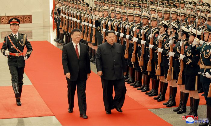 North Korean leader Kim Jong Un and Chinese President Xi Jinping inspect honor guards, as he paid an unofficial visit to Beijing, China, in this undated photo released by North Korea's Korean Central News Agency (KCNA) in Pyongyang March 28, 2018. (KCNA/via Reuters)