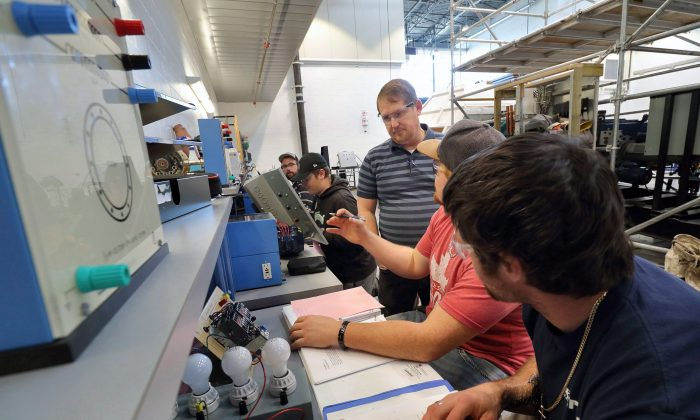 Colin Winder, instructor of the wind turbine technician program at Lethbridge College, provides practical training for students on Nov. 15, 2017, in Lethbridge, Alberta. Unpredictable physical work is less vulnerable to automation. (The Canadian Press/David Rossiter)