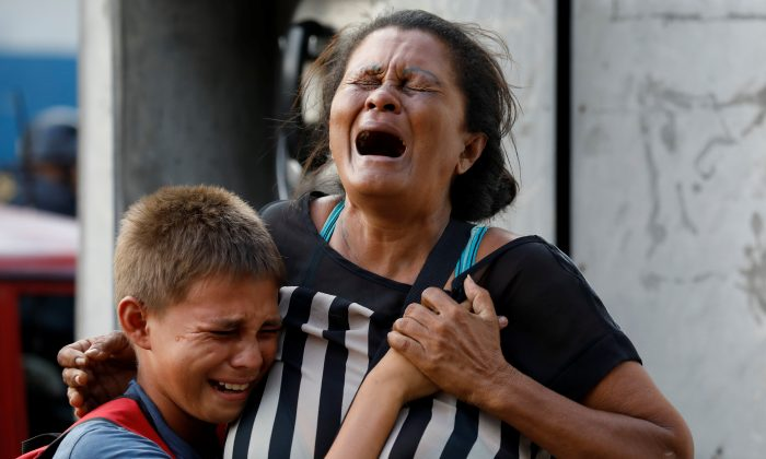 Relatives of inmates held at the General Command of the Carabobo Police react as they wait outside the prison, where a fire occurred in the cells area, according to local media, in Valencia, Venezuela March 28, 2018. (Reuters/Carlos Garcia Rawlins)