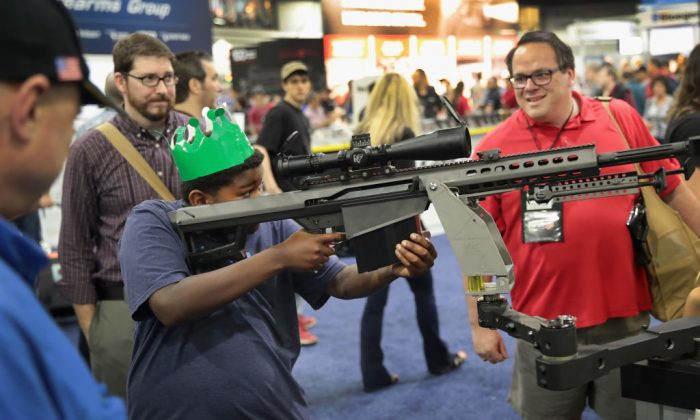 National Rifle Association members look over guns in the Barrett display at the 146th NRA Annual Meetings & Exhibits in Atlanta, Georgia, on April 29, 2017. With more than 800 exhibitors, the convention is the largest annual gathering for the NRA's more than 5 million members. (Scott Olson/Getty Images)