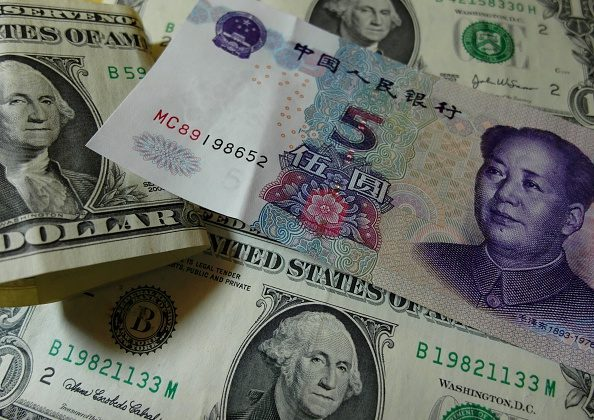 Yuan banknotes and US dollars are seen on a table in Yichang, central China's Hubei province on August 14, 2015.   (STR/AFP/Getty Images)