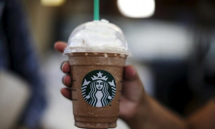 A woman holds a Frappuccino at a Starbucks store inside the Tom Bradley terminal at LAX airport in Los Angeles, California, Oct. 27, 2015. (Reuters/Lucy Nicholson)