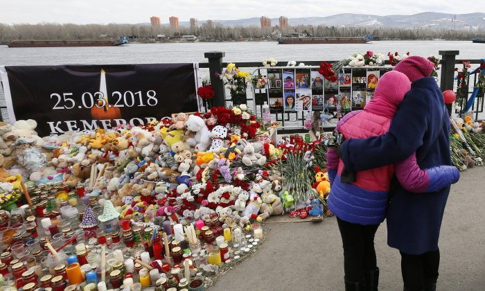 People visit a makeshift memorial on the day of national mourning for the victims of a shopping mall fire in Kemerovo on an embankment of the Yenisei River in the Siberian city of Krasnoyarsk, Russia, March 28, 2018. (Reuters/Ilya Naymushin/File Photo)