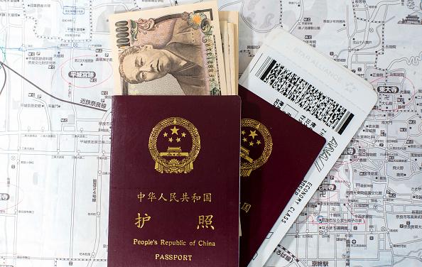 Chinese passport, Japanese Yen and flight tickets. (Zhang Peng/LightRocket via Getty Images)