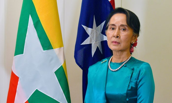 Burma's State Counsellor Aung San Suu Kyi stands next to national flags of Australia and Burma at Parliament House in Canberra, Australia, March 19, 2018.    (AAP/Mick Tsikas/via Reuters)