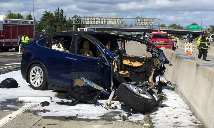 Rescue workers attend the scene where a Tesla electric SUV crashed into a barrier on U.S. Highway 101 in Mountain View, California, on March 25, 2018. (KTVU FOX 2/via Reuters)
