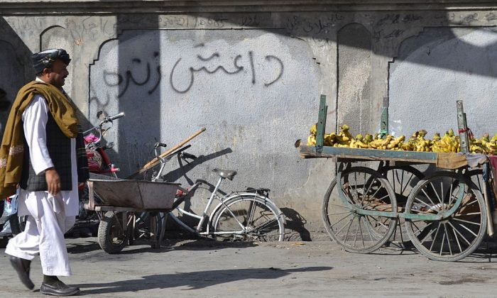 A Pakistani pedestrian walks past a wall graffiti which reads Daesh, the arabic acronym for ISIS, in Quetta in Baluchistan province on November 24, 2014. (Banaras Khan/AFP/Getty Images)