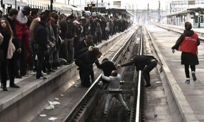 People help a woman who fell onto a railtrack in Gare de Lyon railway station in Paris on April 3, 2018, at the start of three months of rolling rail strikes. Staff at state rail operator SNCF walked off the job from 7.00 pm (1700 GMT) on April 2, the first in a series of walkouts affecting everything from energy to garbage collection. (Christophe Simon/AFP/Getty Images)