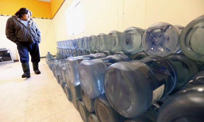 Stewart Redsky, former chief and current alcohol/drug counsellor of Shoal Lake 40 First Nation, walks past one week's worth of 20-litre water bottles in the community's water storage room on February 25, 2015. (The Canadian Press/John Woods)