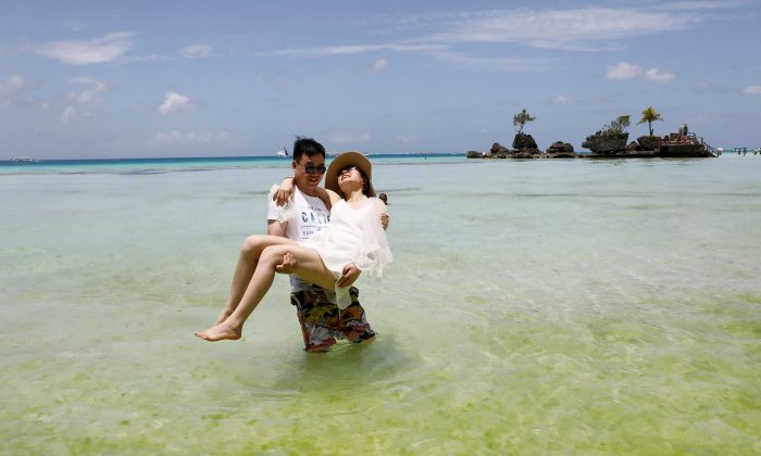 Newly-wed tourists frolic in the beach of Boracay in Philippines, April 8, 2018. (Reuters/Erik De Castro)