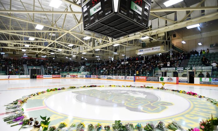Flowers lie on the ice as people gather for a vigil at the Elgar Petersen Arena, home of the Humboldt Broncos, to honour the victims of a fatal bus accident in Humboldt, Saskatchewan, April 8, 2018. (Jonathan Hayward/Pool via Reuters)