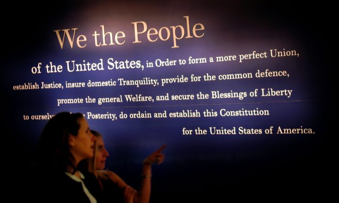 Two women walk past a painting of the beginning of the U.S. Constitution during a preview of the National Constitution Center in Philadelphia, Penn., on July 1, 2003.  William Thomas Cain/Getty Images