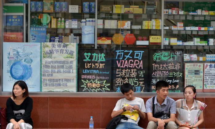 Chinese shoppers wait outside a pharmacy in Beijing, China, on Aug. 13, 2013. China imposes high tariffs on imported medicines, which has made it difficult for many citizens to afford treatment for their illnesses. (Mark Ralston/AFP/Getty Images)