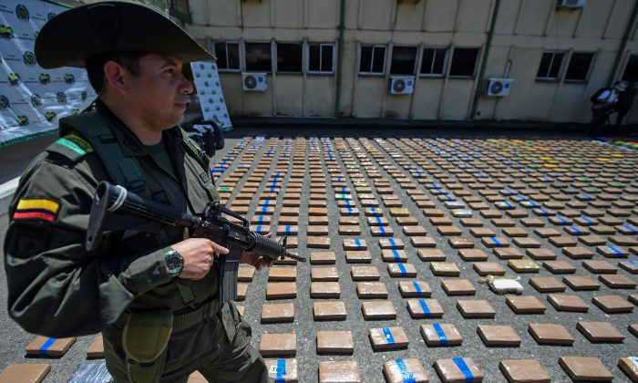 A member of the Colombian antinarcotics police, stands guard beside a one-ton shipment of cocaine seized to the country's biggest drug gang, the Gulf Clan in a container with destination to Europe in Buenaventura, Colombia's main port on the Pacific Ocean, on Aug. 10, 2017. (RAUL ARBOLEDA/AFP/Getty Images)