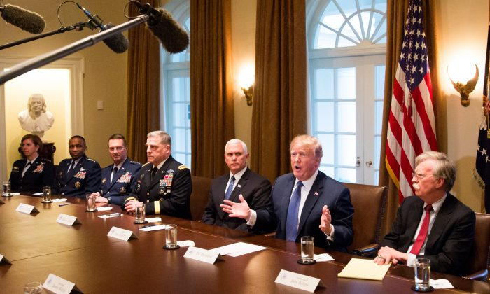 President Donald Trump speaks during a meeting with senior military leaders while flanked by Vice President Mike Pence (L) and National Security Advisor John Bolton (R) in the Cabinet Room of the White House in Washington on April 9, 2018. (Samira Bouaou/The Epoch Times)