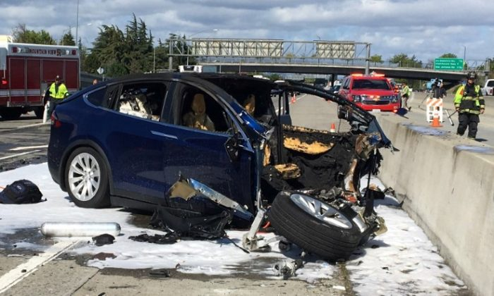 FILE PHOTO: Rescue workers attend the scene where a Tesla electric SUV crashed into a barrier on U.S. Highway 101 in Mountain View, California, Mar. 25, 2018. (KTVU FOX 2/via REUTERS)